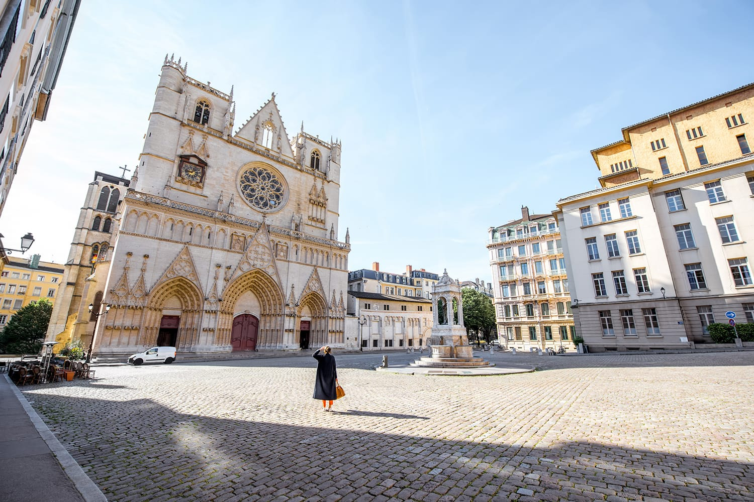 Morning view on the saint John cathedral with woman walking on the square in the old town of Lyon city