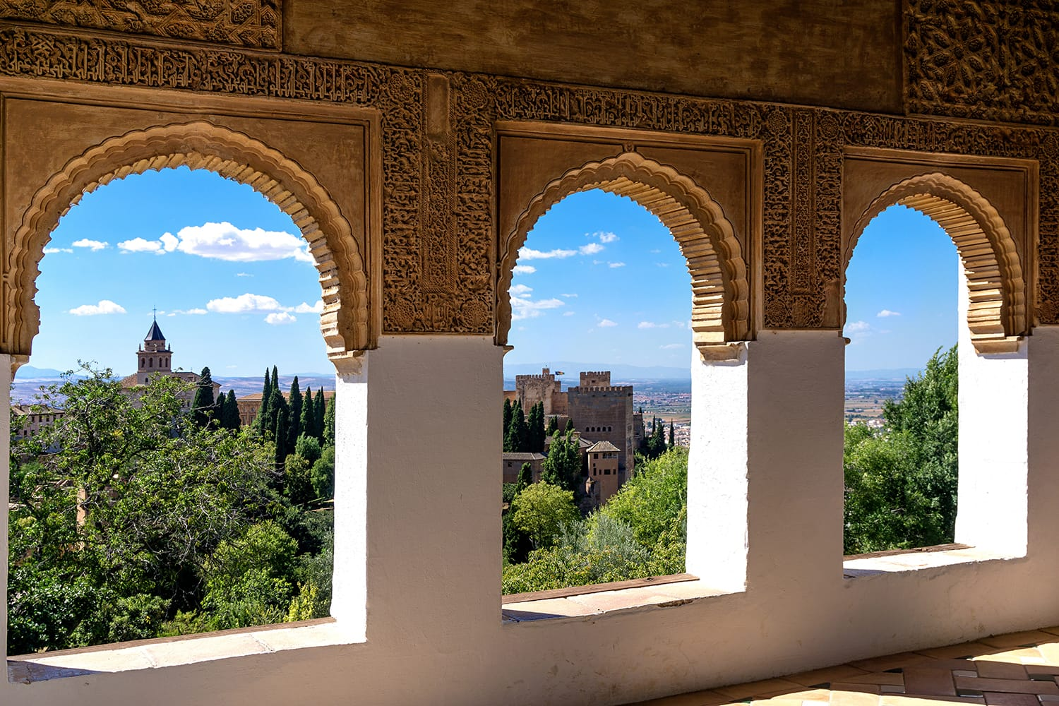 Stone arches in the world-famous Alhambra in Granada with beautiful views of the fortress and Granada, Spain