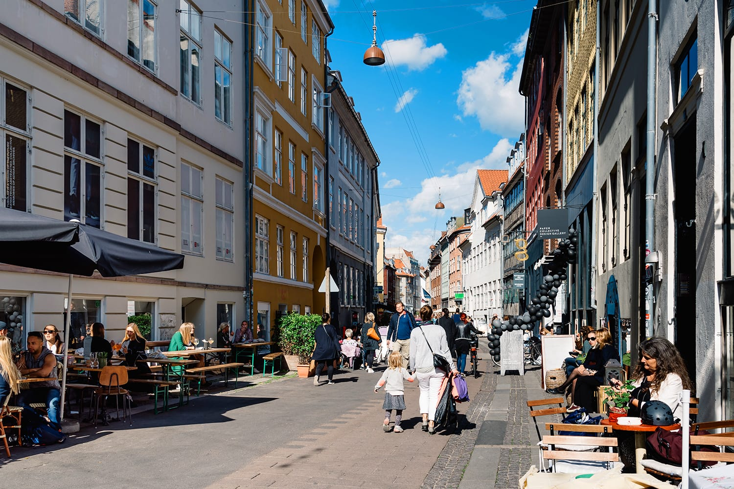 Stroget Street. Commercial street with sidewalk cafe in historical city centre of Copenhagen a sunny day of summer. Denmark