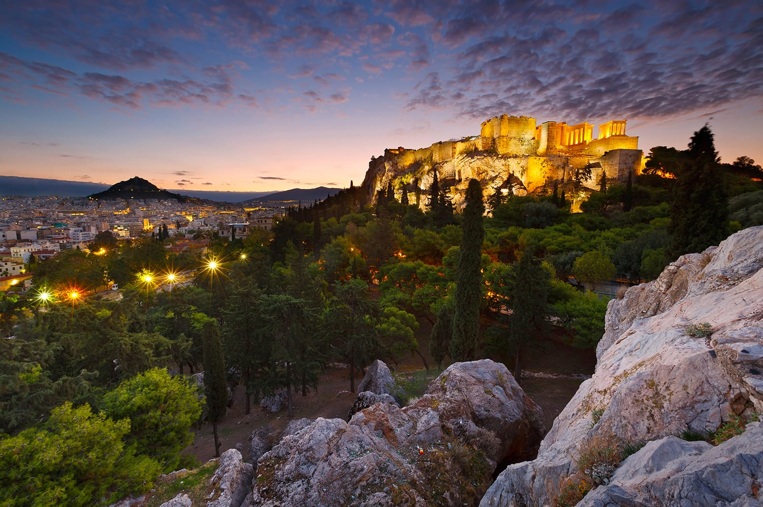 Sunset view of Acropolis and Lycabettus Hill from Areopagus hill in Athens, Greece