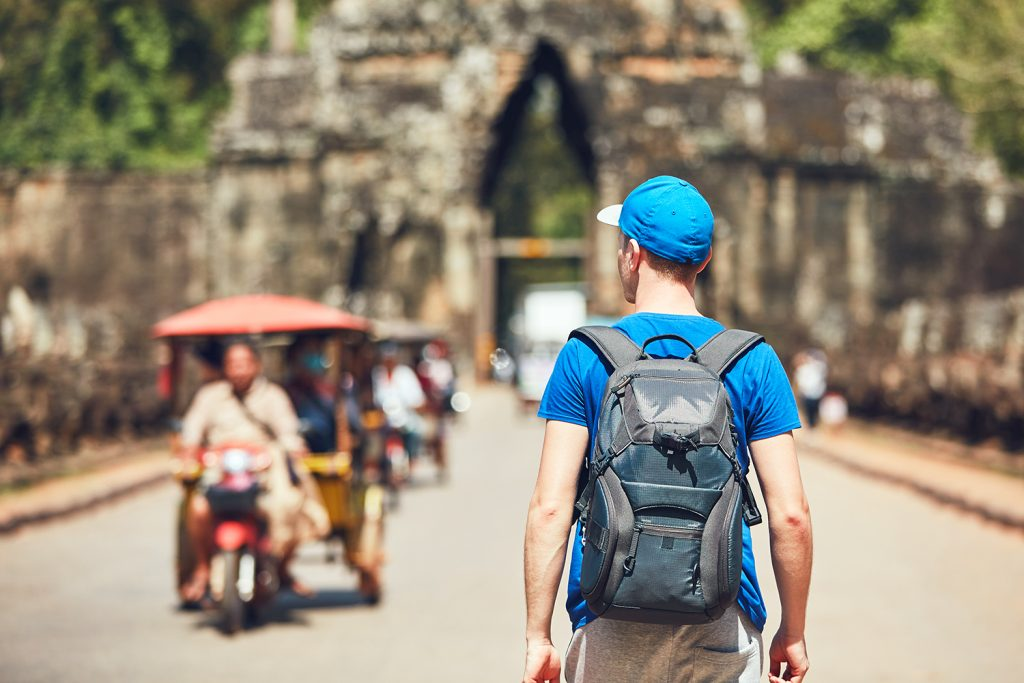 ourist in the ancient city. Young man with backpack coming to ancient monuments. Siem Reap, Cambodia