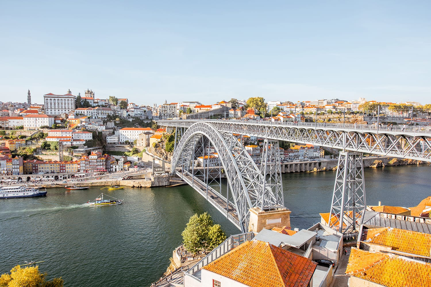 Landscape view the beautiful old town with famous iron bridge above the Douro river during the sunset in Porto city, Portugal