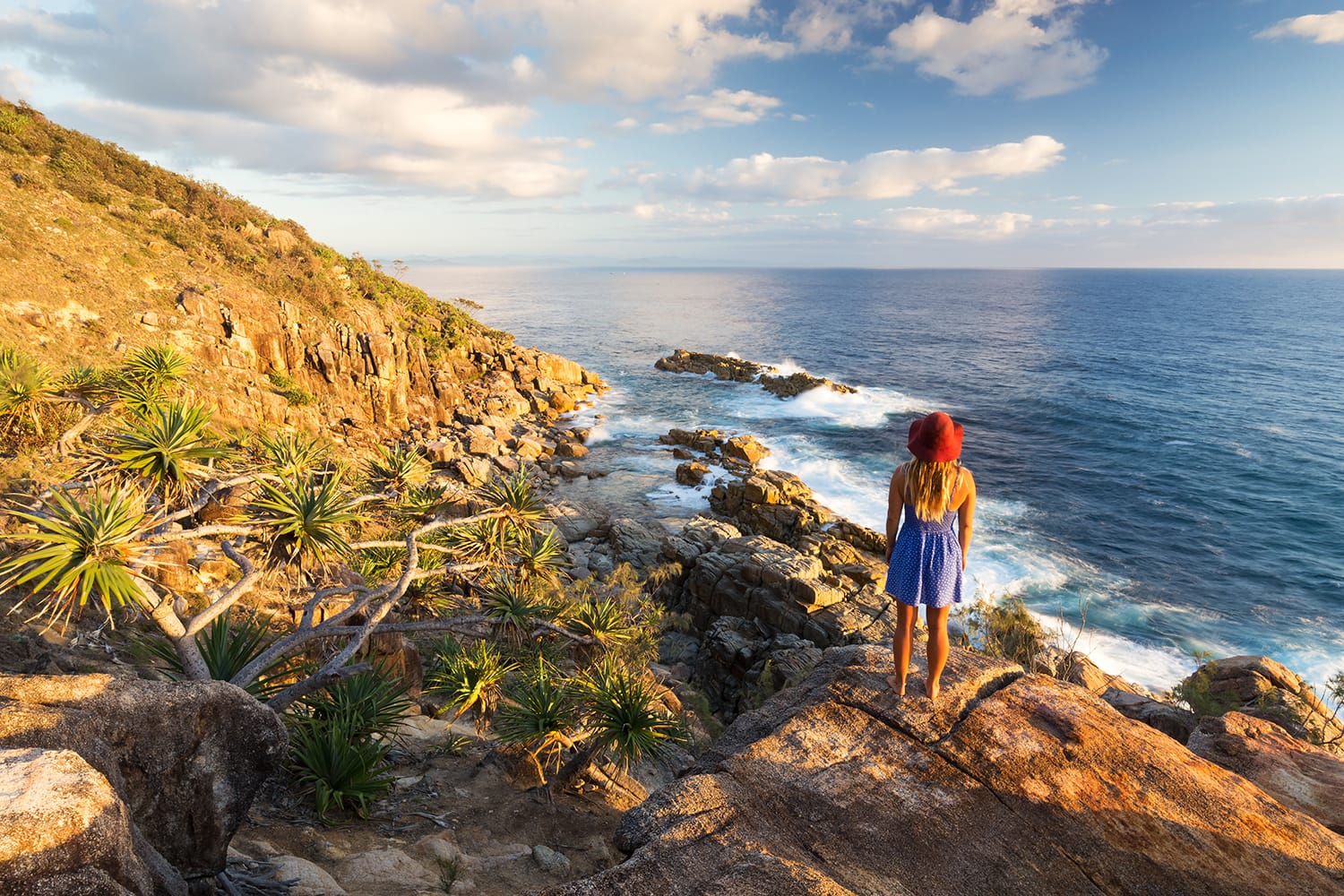 A young woman admires a coastal view at sunrise near Coffs Harbour, Australia.