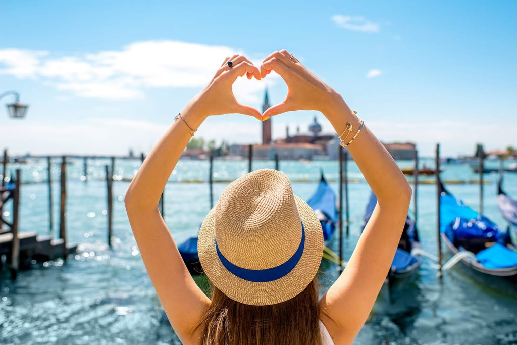 Woman making heart shape with hands on the beautiful view in Venice, Italy