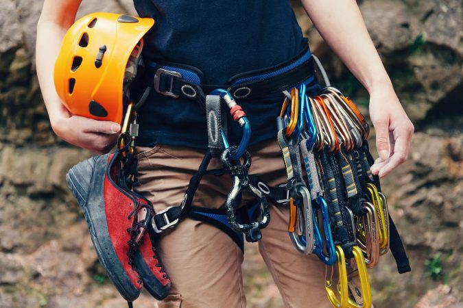 Woman standing with climbing equipment and helmet outdoor, front view.