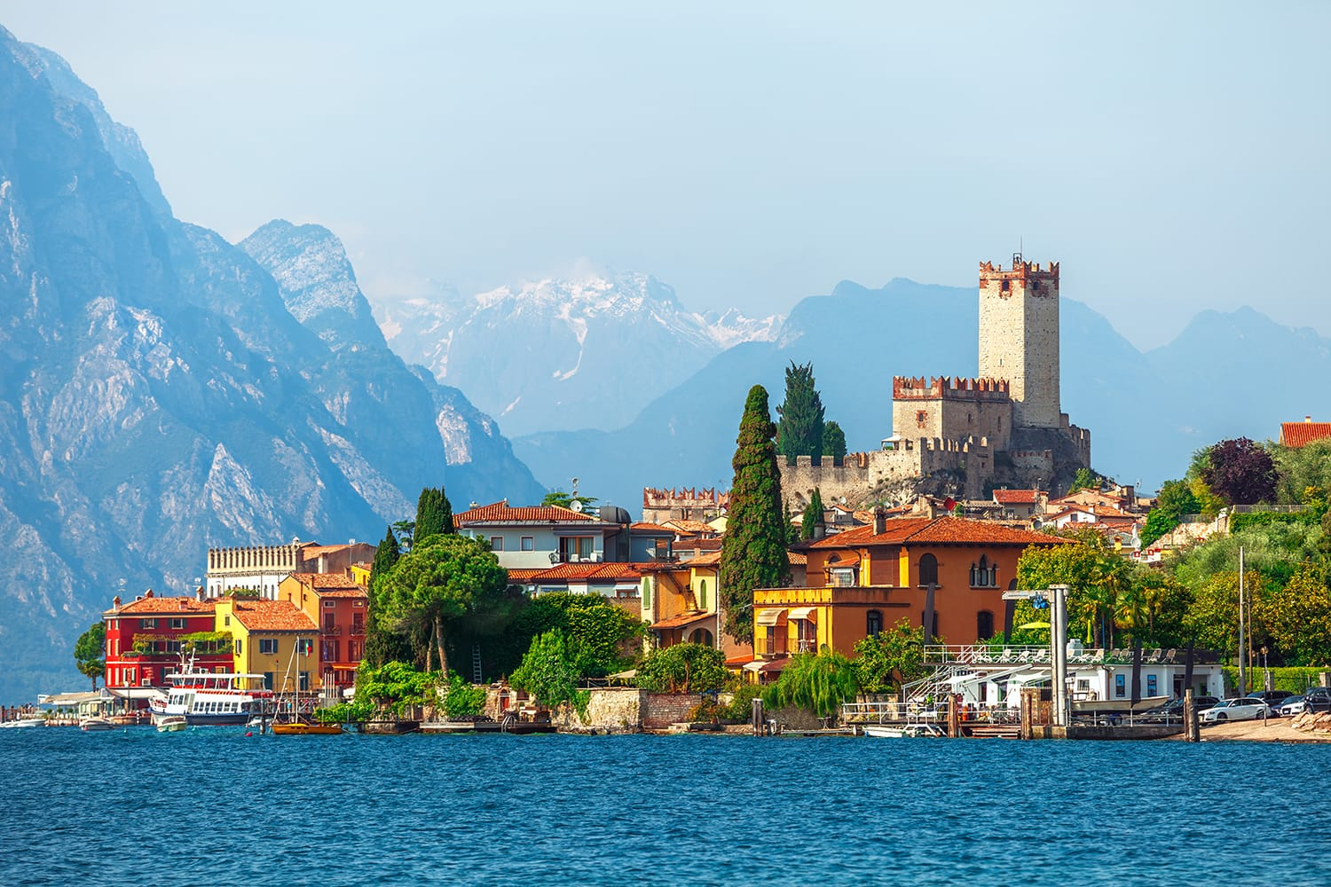 Malcesine town. Ancient tower and fortress in old town malcesine at Garda Lake, Veneto region, Italy. High snowbound top mountains on background summer landscape with colorful houses of Malcesine bank