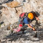 Man wearing helmet climbing rock