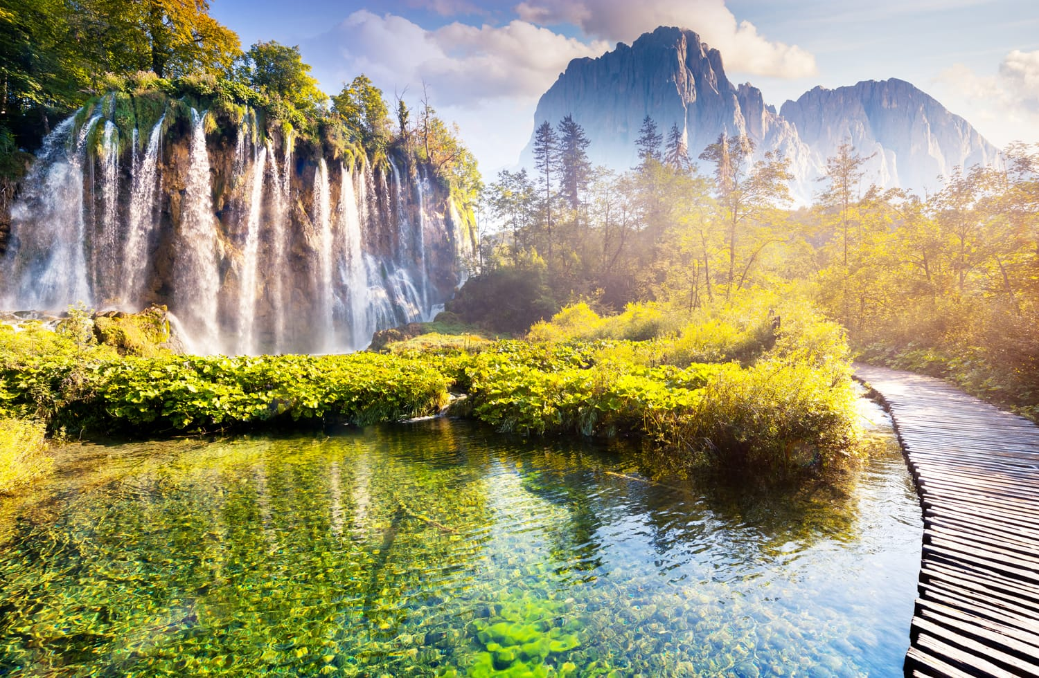Majestic view on waterfall with turquoise water, sunny beams in the Plitvice Lakes National Park, Croatia.