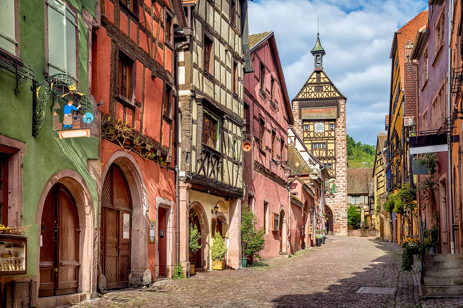 Central street of Riquewihr village with colorful traditional half-timbered french houses and Dolder Tower, Alsace, France