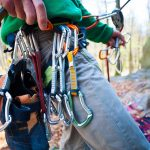 Climber partner insures. Quickdraw, carabiner, and climbing shoes hanging on a safety system