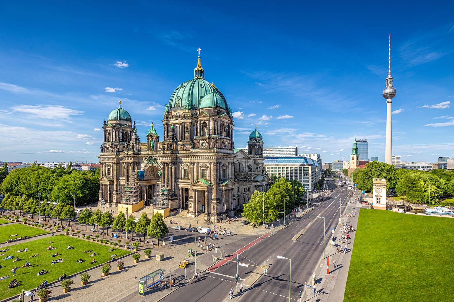 Aerial view of Berlin Cathedral at Lustgarten park with famous TV tower in the background on a sunny day with blue sky and clouds in summer, Berlin Mitte district, Germany