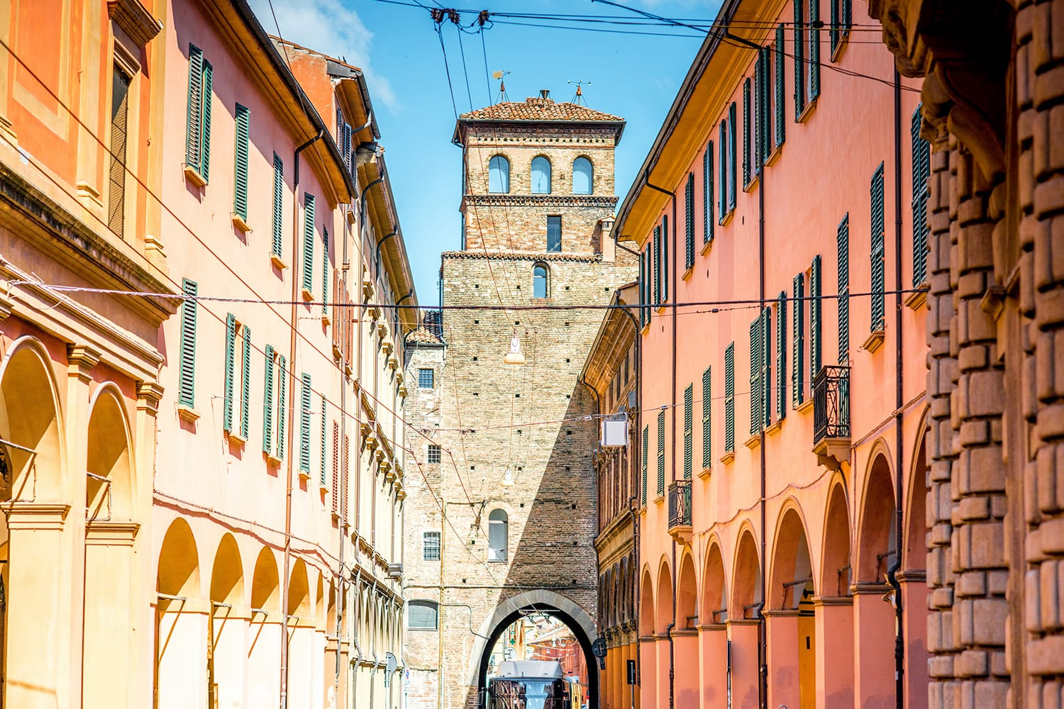Street view with city gate and galleries in Bologna in Italy