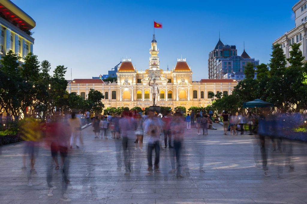 People are walking and taking pictures in front of the City Hall building, Ho Chi Minh City, Vietnam.