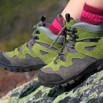 Hiking boots and mountain rocks background