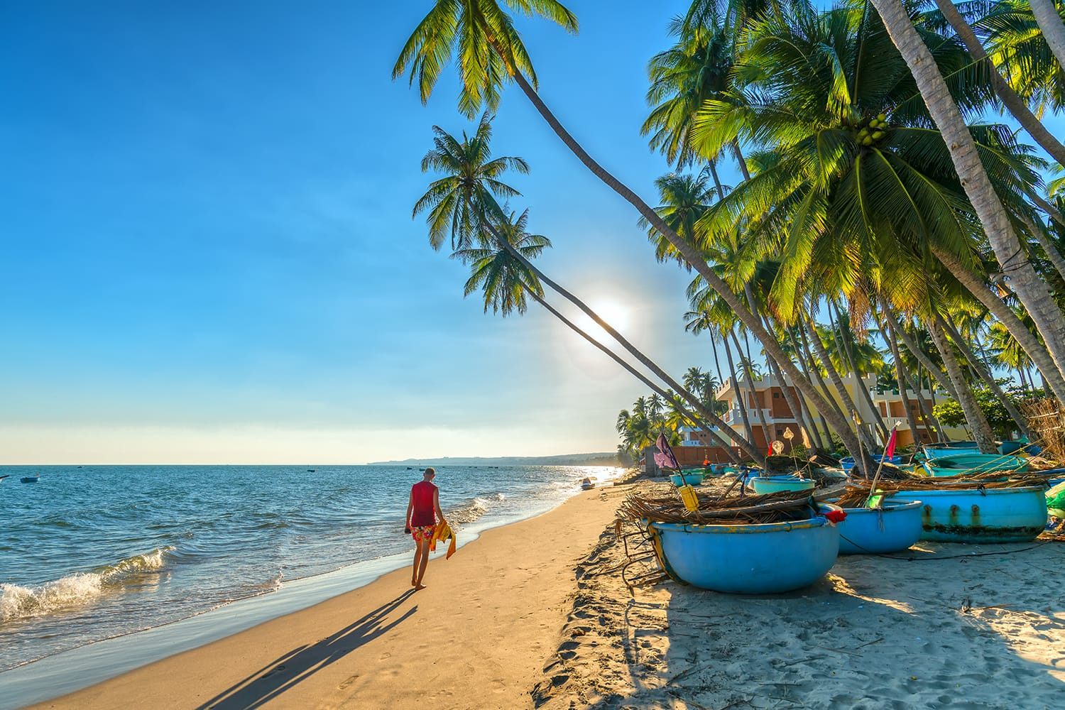 The man alone go to end of tropical beach with coconut palm trees as sun gradually create beautiful setting for weekend guests at paradise beach in Mui Ne, Vietnam