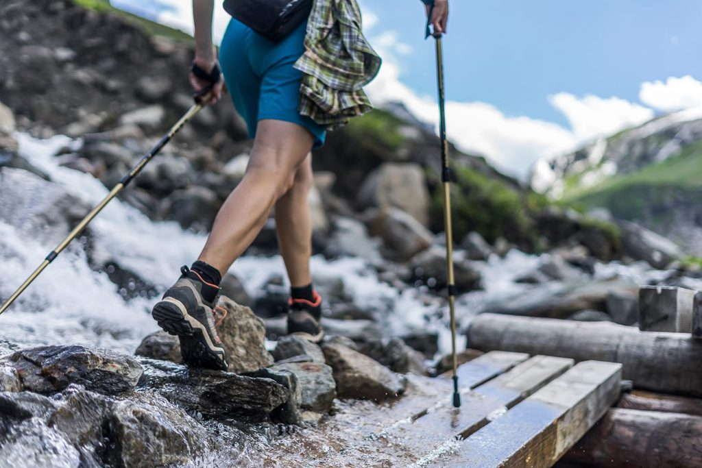 Woman wearing outdoor boots and shorts walking across a wooden bench and rocks crossing a wild alpine creek using hiking poles. Trekking shoes on rocks and in runnig water.