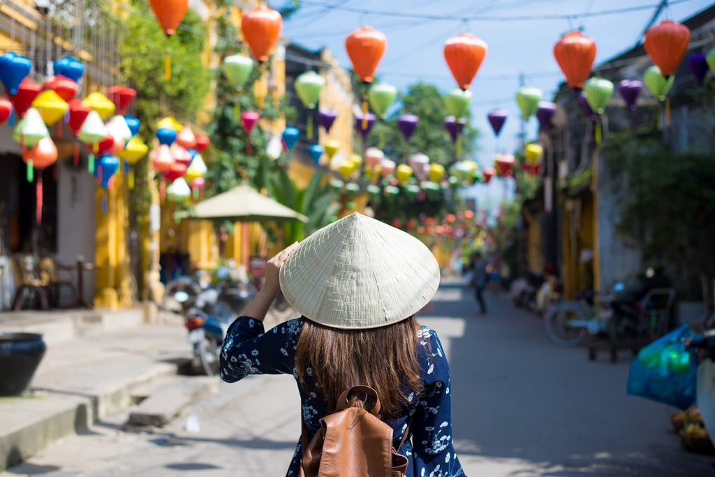 Tourist woman is wearing Non La (Vietnamese tradition hat) and enjoy sightseeing at Heritage village in Hoi An city in Vietnam