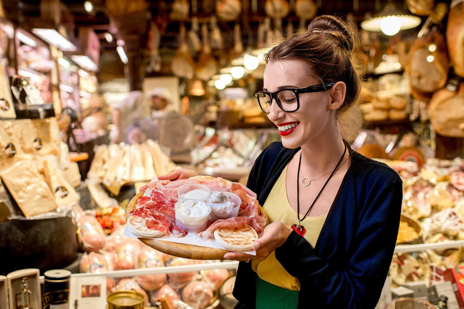 Young woman sitting near the food shop with traditional italian appetizer on the blurred food showcase background in Bologna city.