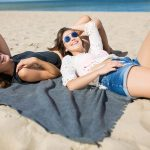 Two happy women lying together on blanket on beach