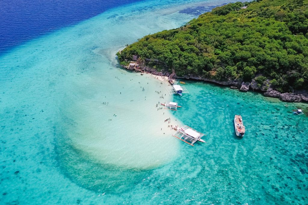 Aerial view of sandy beach with tourists swimming in beautiful clear sea water of the Sumilon island beach landing near Oslob, Cebu, Philippines