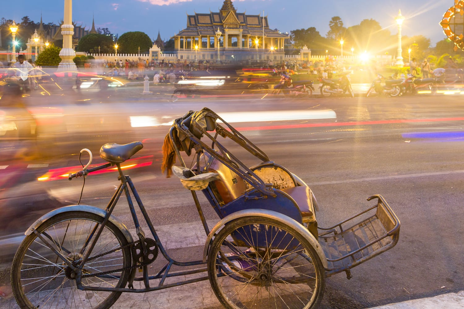 A bicycle rickshaw is parked in front of Phnom Penh Royal Palace in Cambodia capital city.