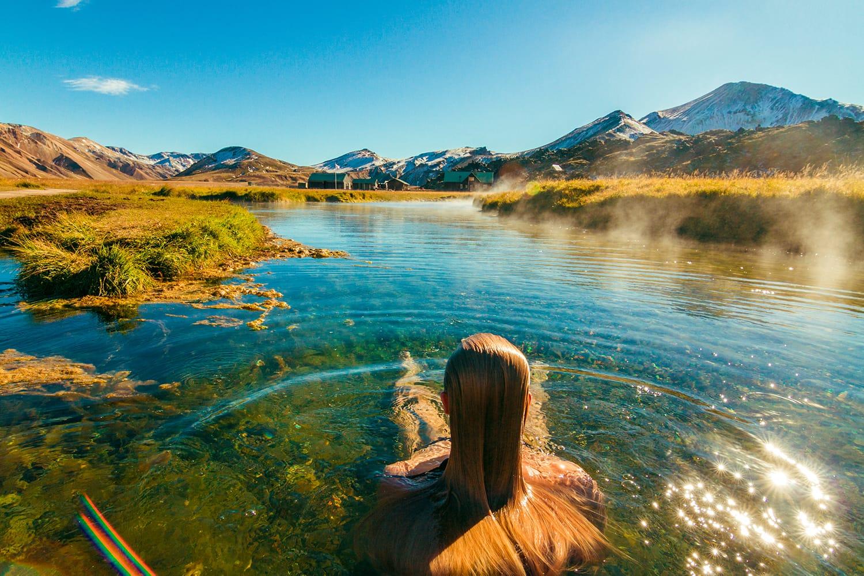 Beautiful female back packer traveler relaxing in the natural hot springs of Landmannalaugar, Iceland