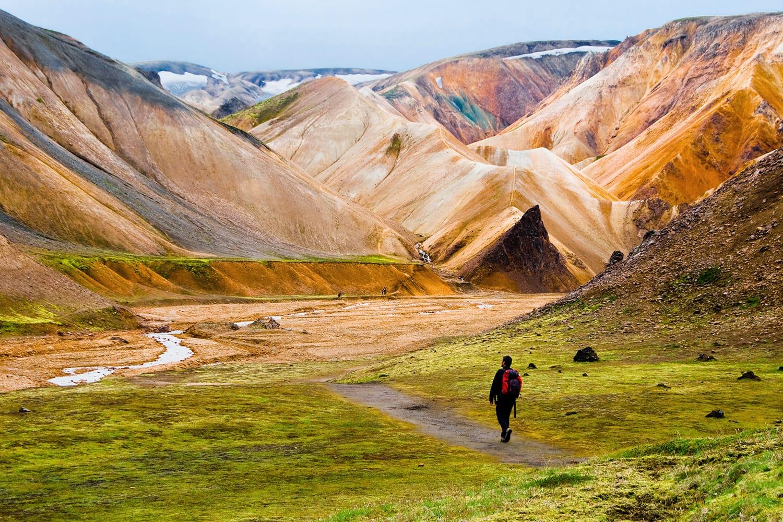 Person hiking at Landmannalaugar colorful mountains in Iceland