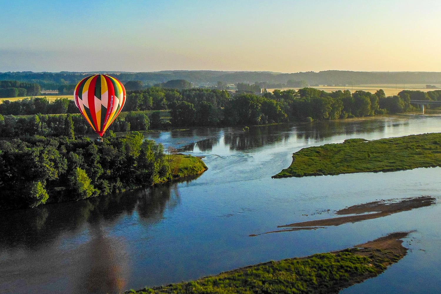 View of a hot air balloon over the Loire River in the early morning