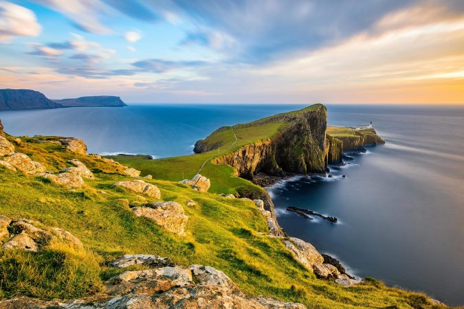 Neist Point Lighthouse on the Isle of Skye bathed in golden light from the setting sun