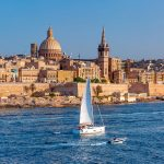 White yacht and Old town of Valletta with churches of Our Lady of Mount Carmel and St. Paul's Anglican Pro-Cathedral, Valletta, Capital city of Malta