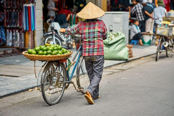 Vendor selling fruits from bicycle in Hanoi, Vietnam