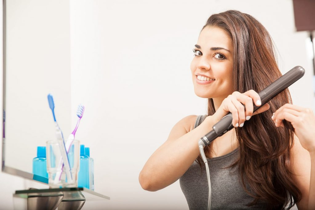 Beautiful young Hispanic woman using a travel flat iron to straighten her hair in the bathroom