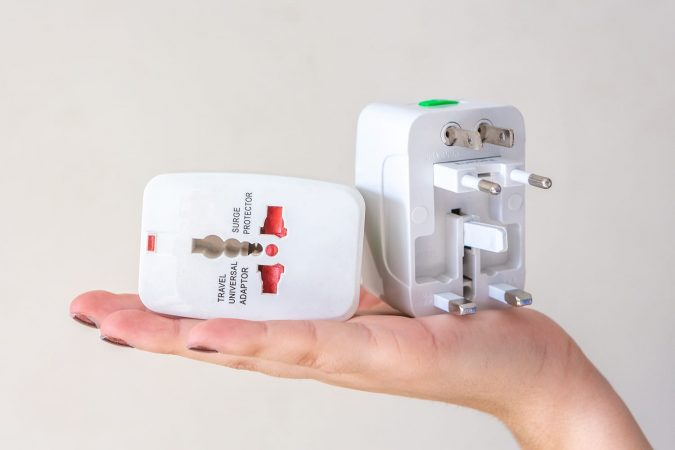 Close up of woman hand holding universal electric socket plug adapters, isolated on white background. Used to connect electrical outlets worldwide