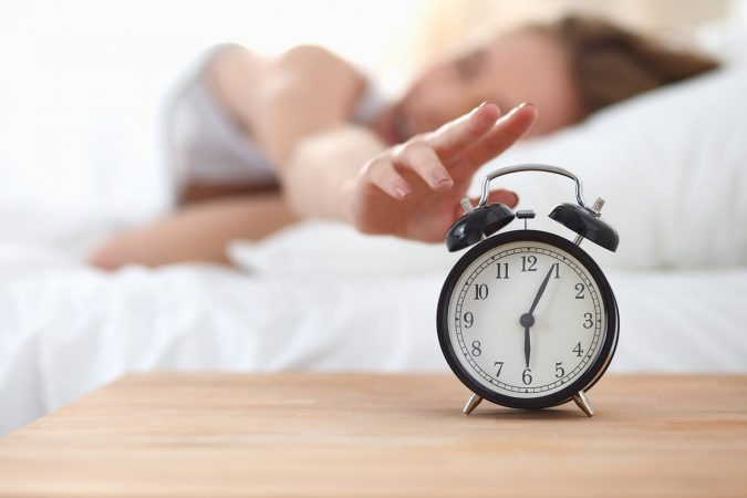 Young sleeping woman and travel alarm clock in bedroom at hotel