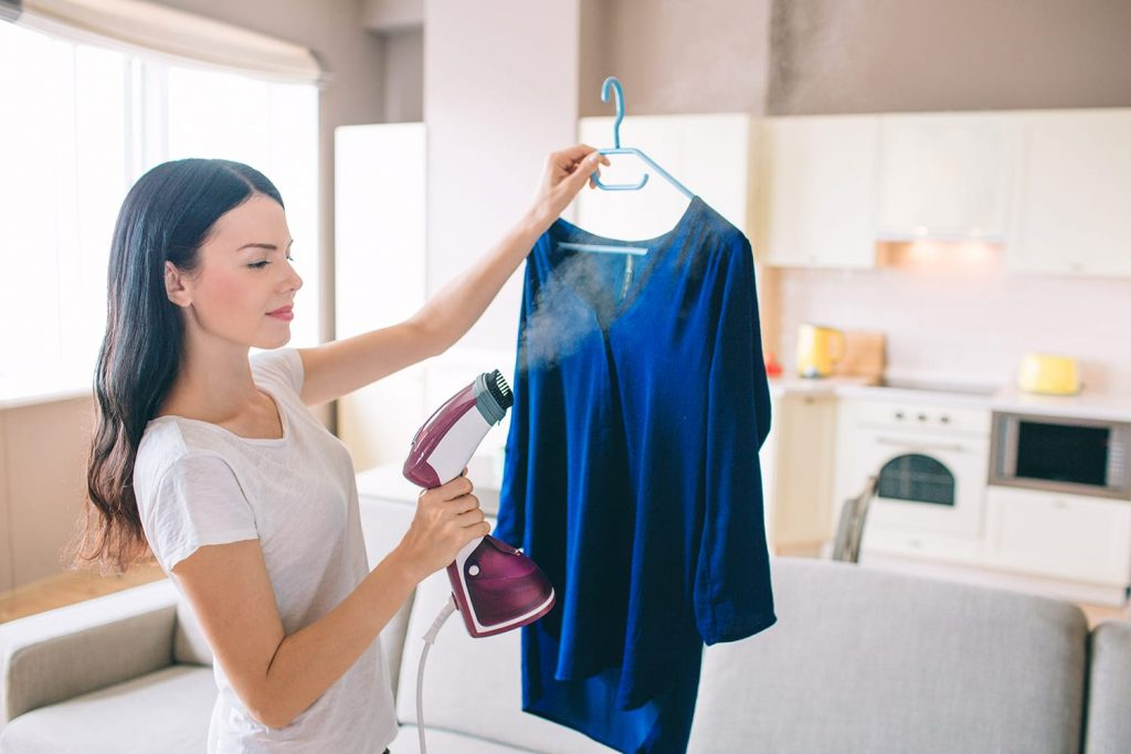 Woman is steaming blue shirt in hotel