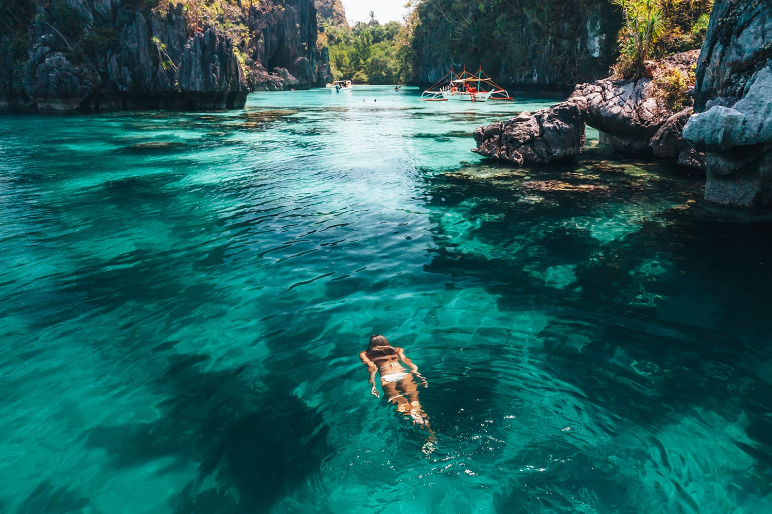 Young woman swimming in clear sea water in lagoon and looking at beautiful landscape. Travelling tour in Asia: El Nido, Palawan, Philippines