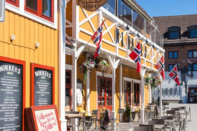 Colorful wooden building with Norwegian flags in Lillehammer, Norway