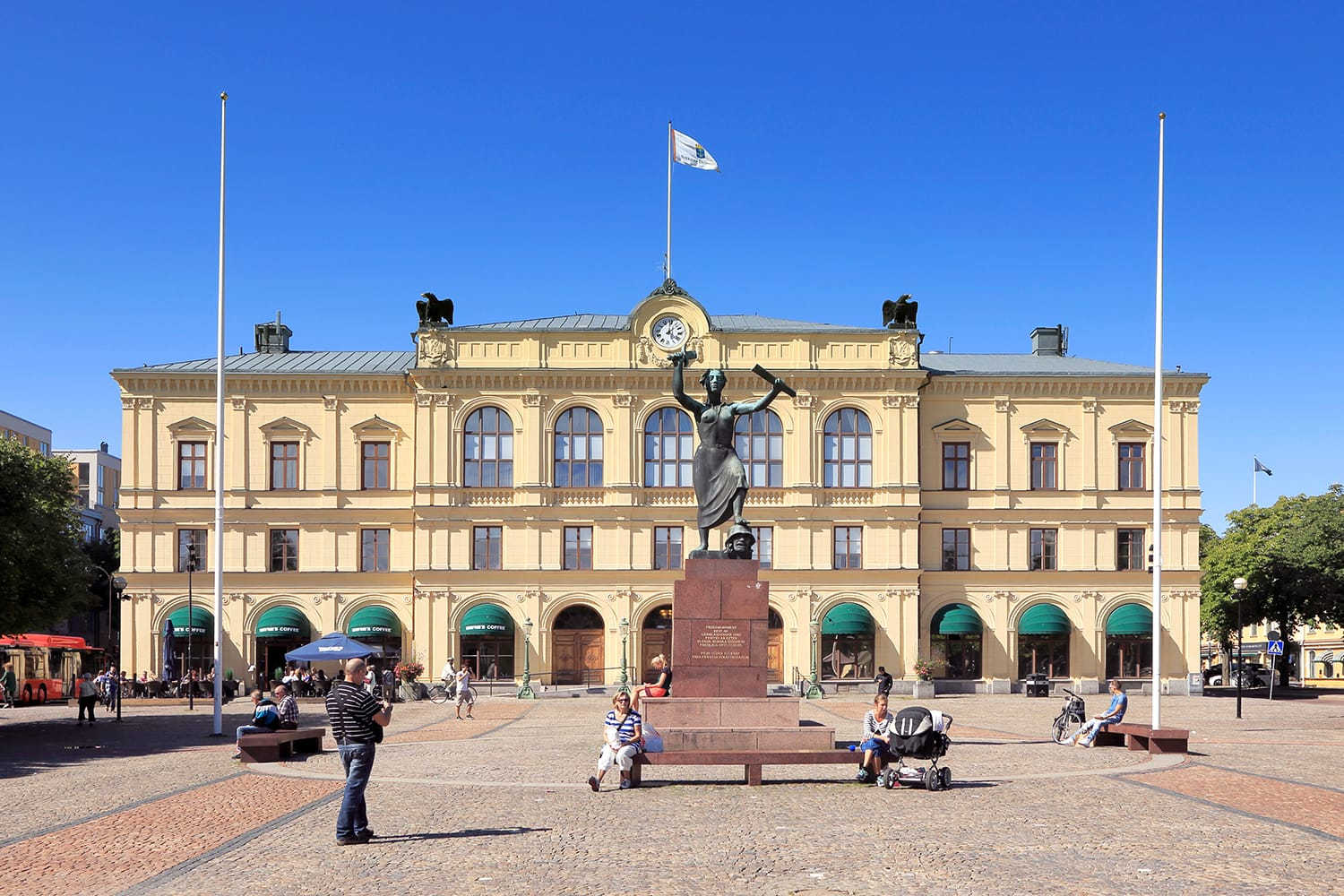 View of the main square with people and the old town hall behind the peace monument Freden during a sunny day with clear blue sky in Karlstad, Sweden