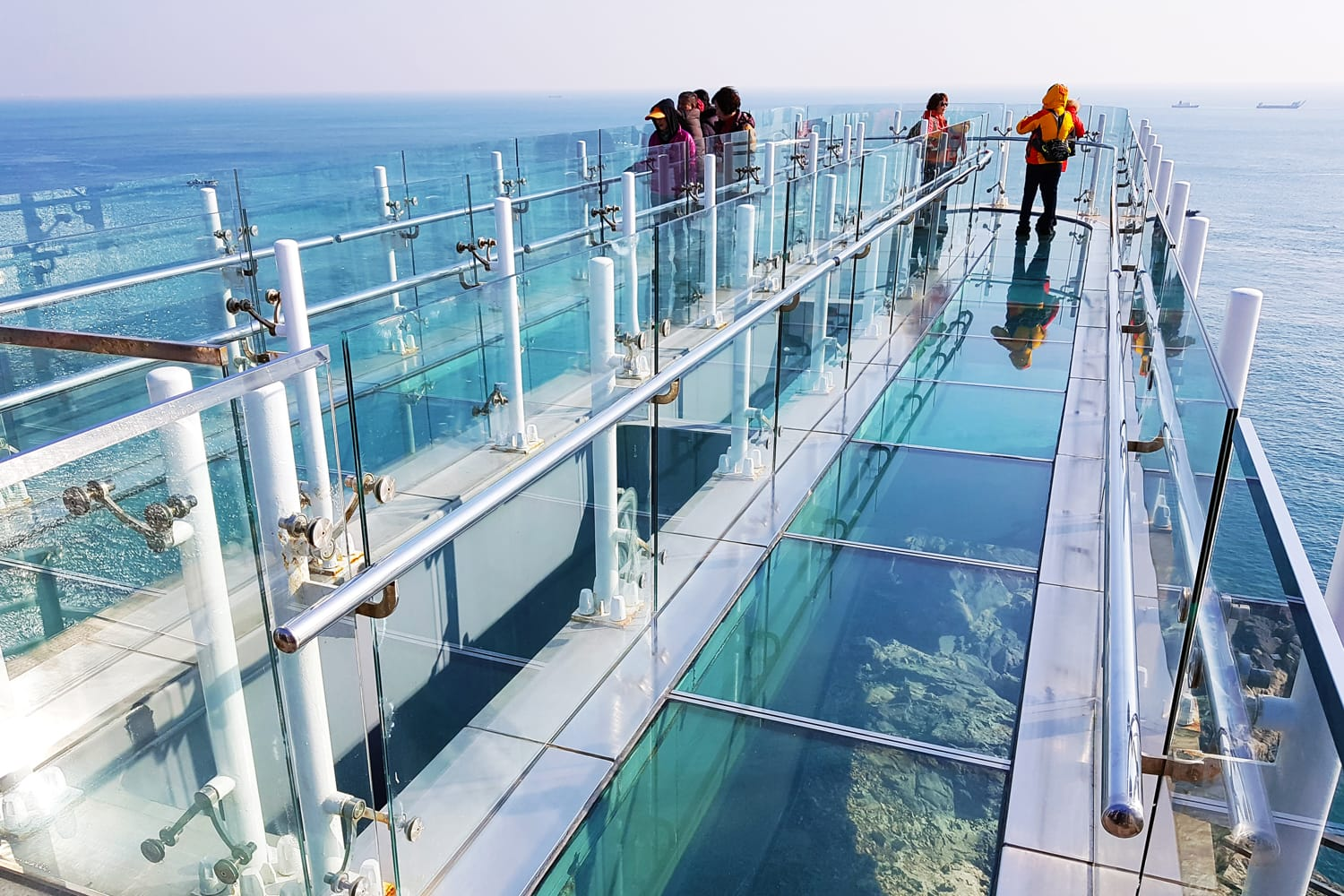 Many tourists standing at Oryukdo Skywalk, the glass bridge seascape viewer, one of famous landmark on the peak of rock mountain in Oryukdo City, South Korea