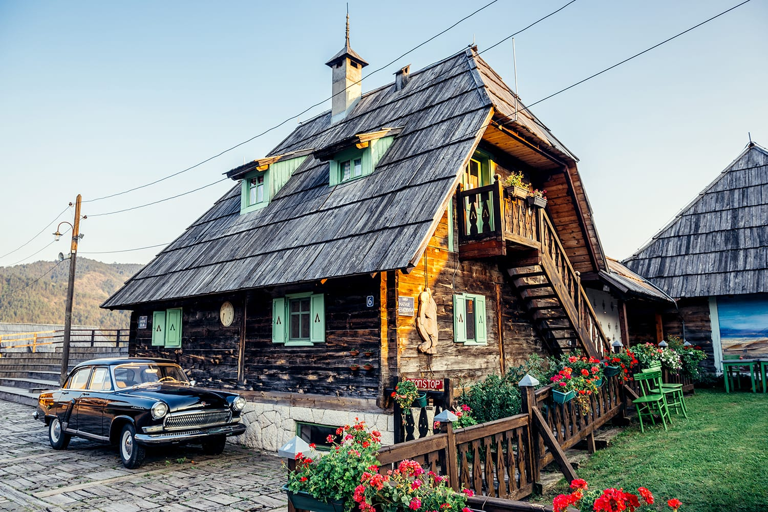 Old Volga car in front of wooden house of Drvengrad village built by Emir Kusturica in Serbia
