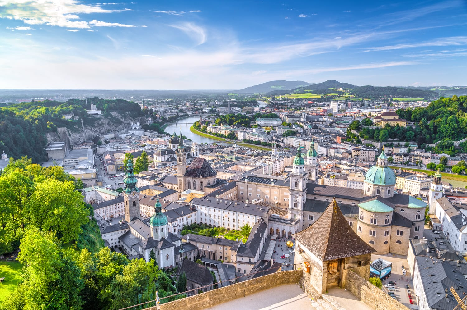 Aerial panoramic view of the historic city of Salzburg with Salzach river in beautiful golden evening light with blue sky and clouds at sunset in summer, Salzburger Land, Austria
