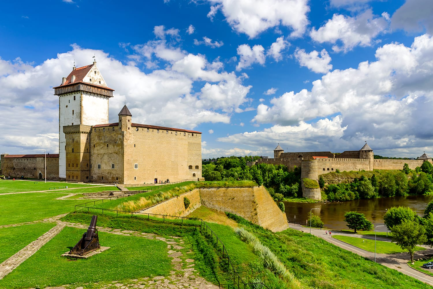 Beautiful summer view of Narva Castle with tall Herman's tower and the ancient Russian fortress in Ivangorod, the monument and popular tourist attraction