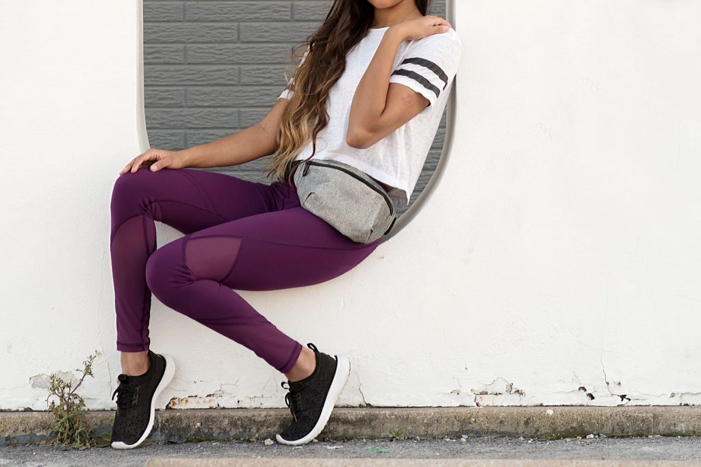 Young Woman Sitting on a White Wall in Sportswear and a Fanny Pack