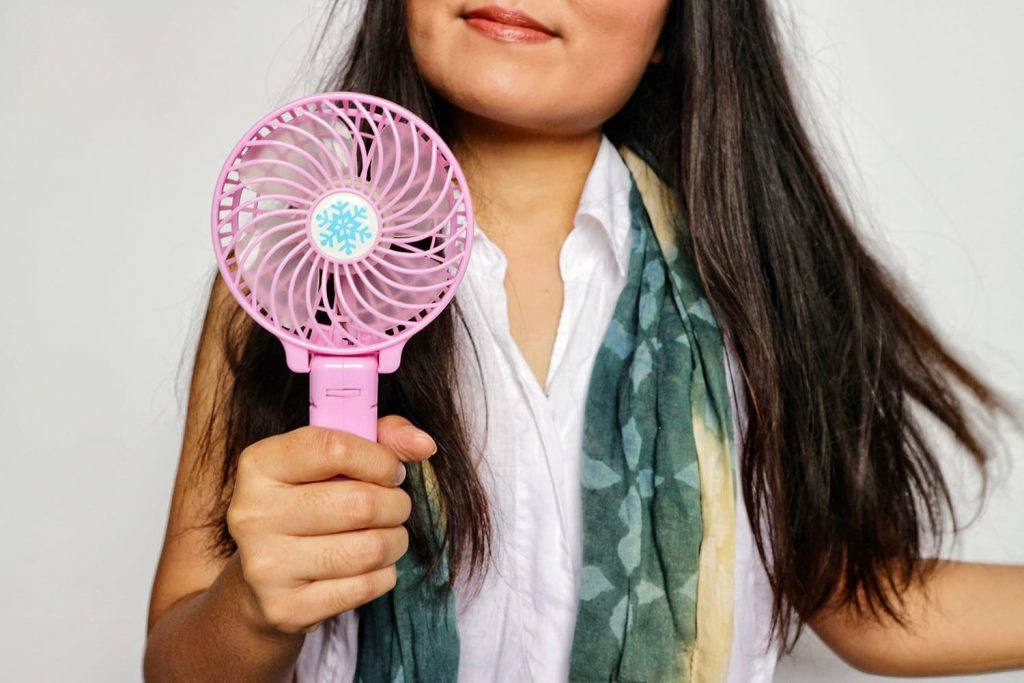 Woman with long brunette hair, wears white shirt with scarf, holding portable pink fan