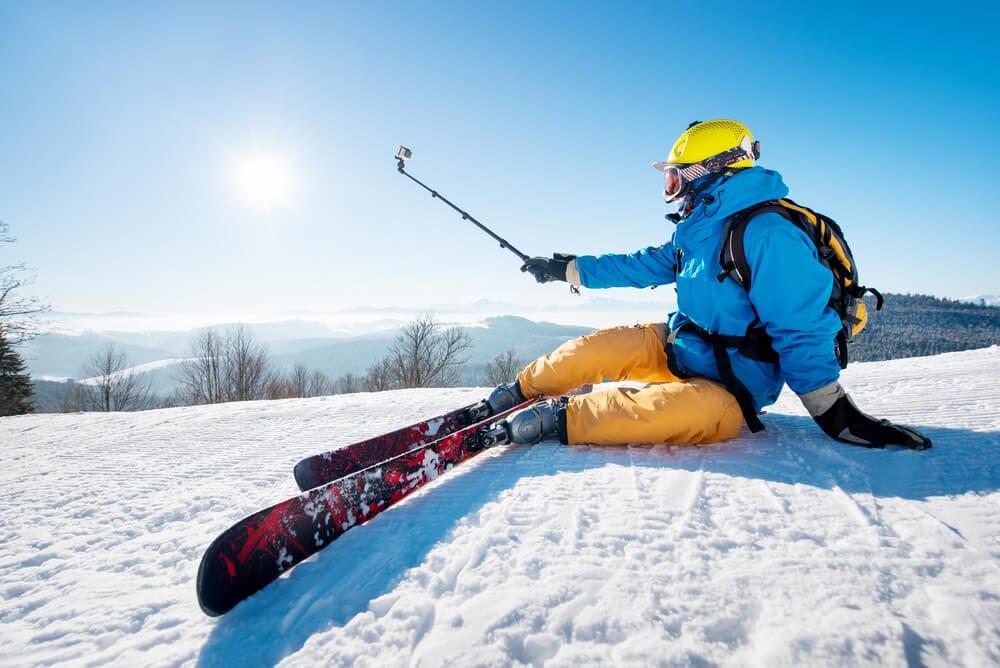 Skier sitting on the ski slope taking a selfie