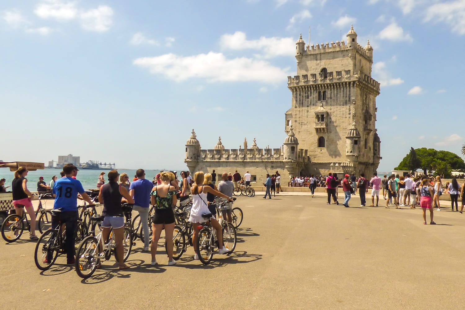 Crowd of tourists and people in bike tours around the Belem Tower, popular landmark in Lisbon, Portugal