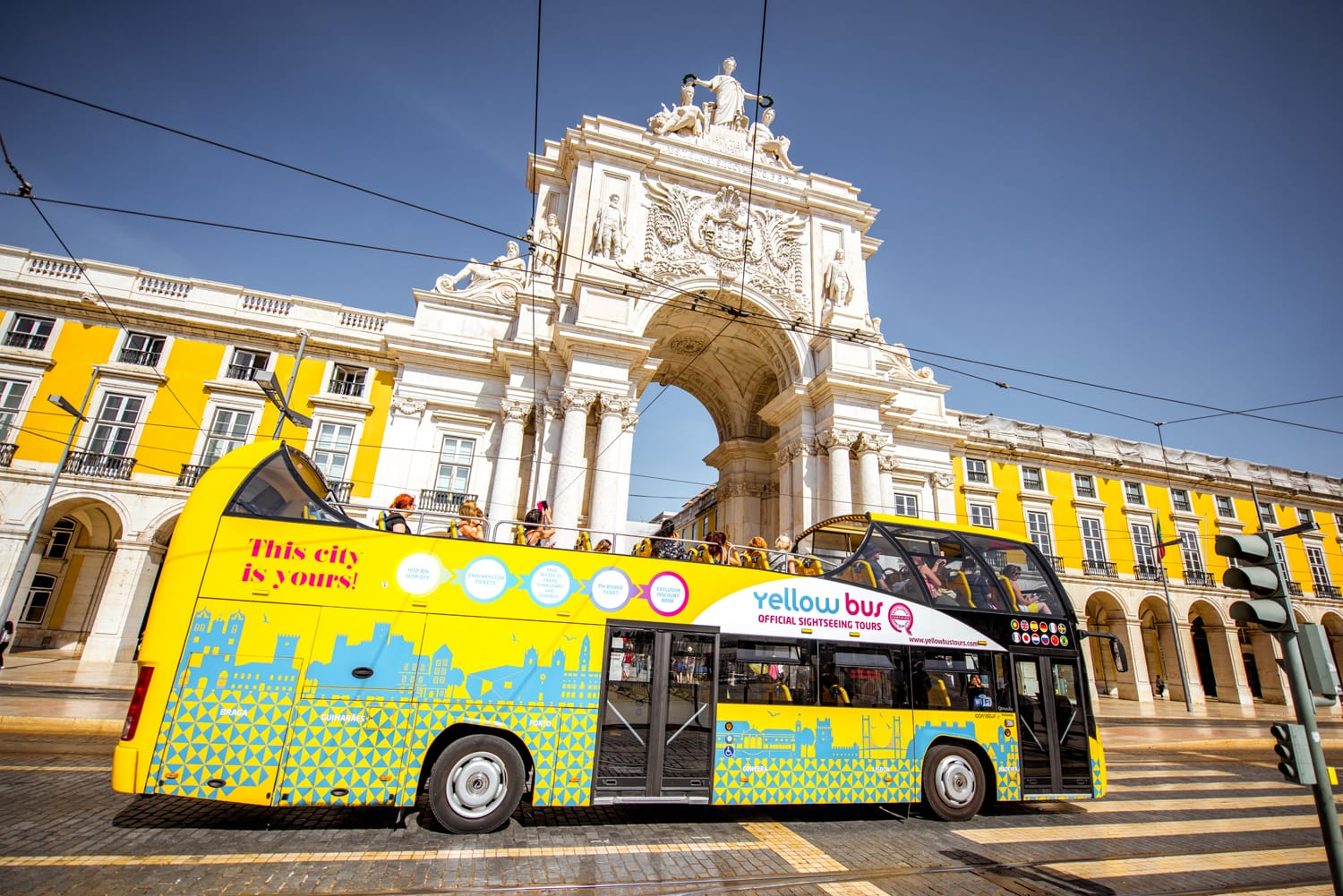 View on the Triumphal arch with tourist bus on the Commerce square during the sunrise in Lisbon city, Portugal