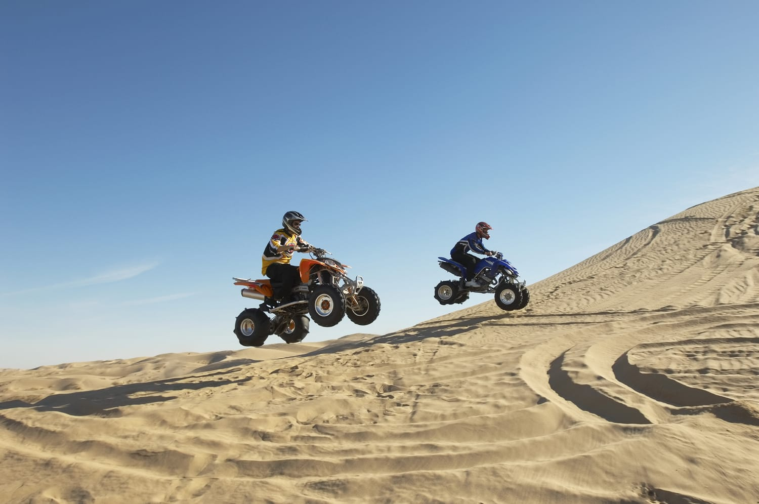Side view of two men doing wheelies on quad bikes in the desert