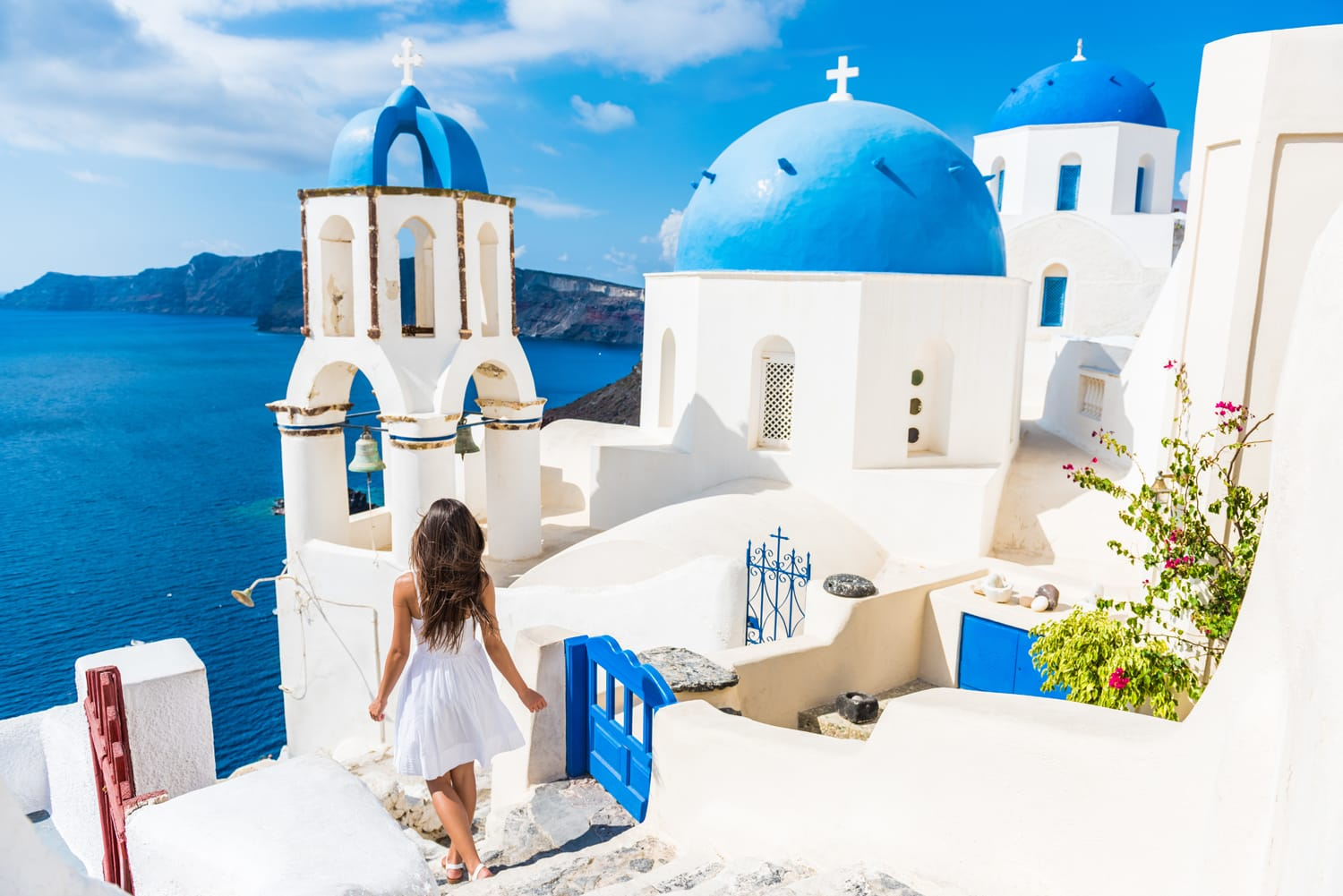 Santorini travel tourist woman on vacation in Oia walking on stairs. Person in white dress visiting the famous white village with the mediterranean sea and blue domes.