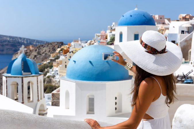 Woman in a white dress is taking photos in Oia, Santorini, Greece